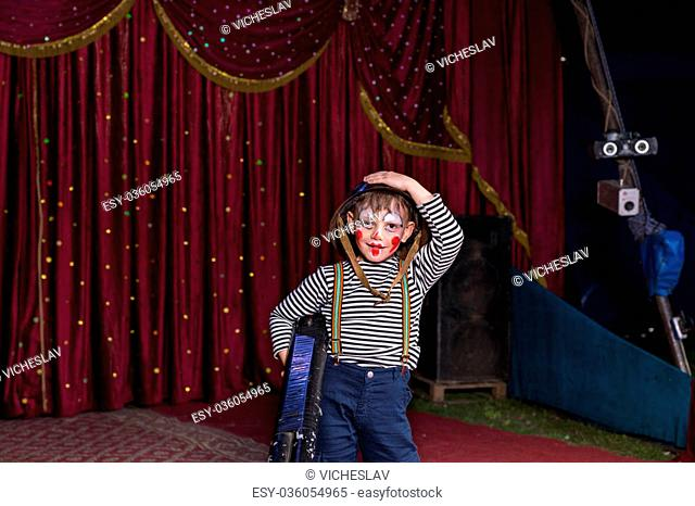 Young Boy Dressed as Clown Wearing Combat Helmet and Striped Shirt Holding Large Gun on Stage with Red Curtain