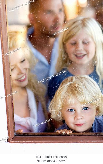 Family standing beside window, smiling