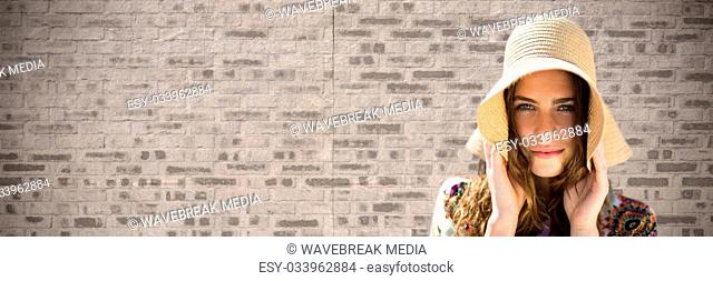 Portraiture of woman holding sun hat against brown brick wall