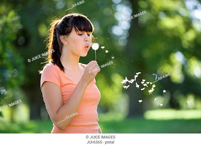 Young woman standing in field, blowing dandelion seeds into air, side view