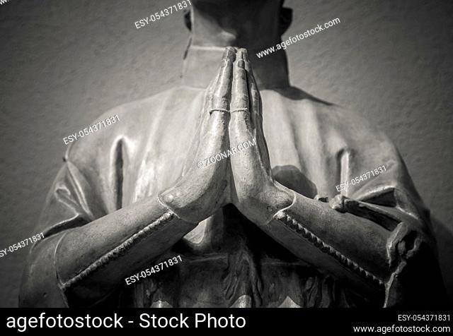 Man hands praying ancient sculpture