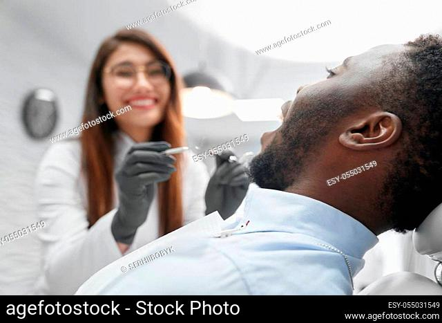 Selective focus of african man in white shirt lying on dental chair with open mouth and looking at female dentist. Pretty doctor keeping dental tools