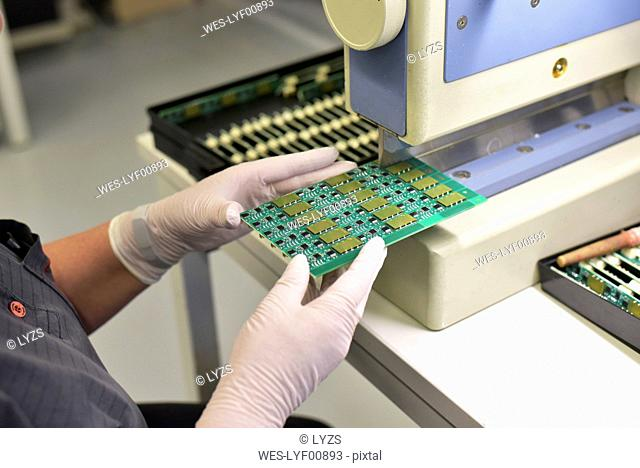 Close-up of woman working on the manufacturing of circuit boards for the electronics industry