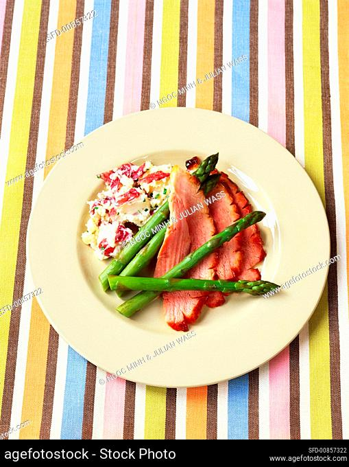 Three slices of roast ham with green asparagus