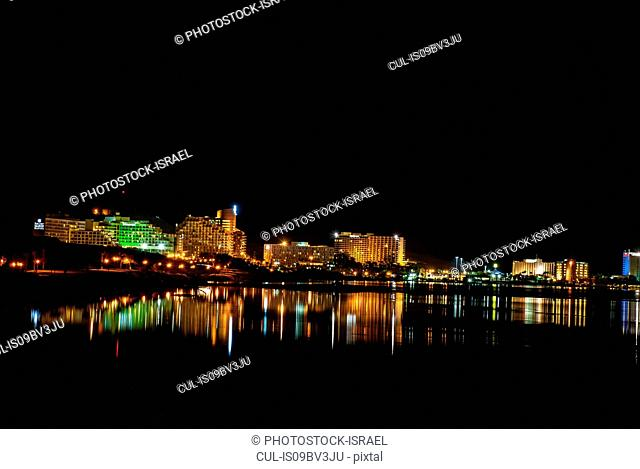 Illuminated hotels, with light reflecting in the Dead Sea at night, Ein Bokek, Israel (view from south)