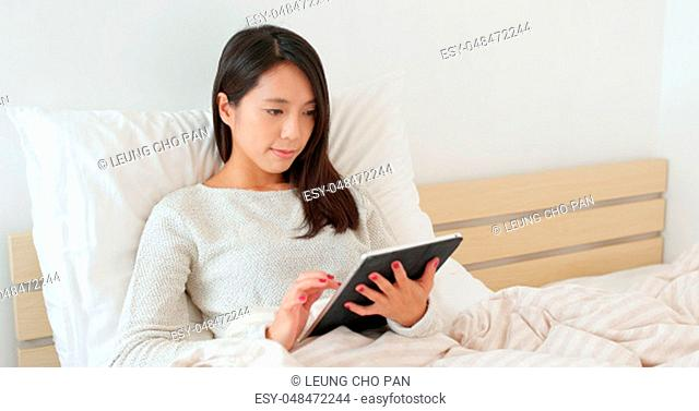 Woman use of tablet on bed