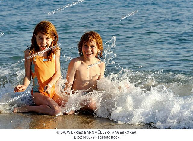 Sister and brother sitting in the water at a beach and having fun in the waves