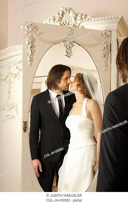 young bridal couple kissing reflected in wardrobe mirror