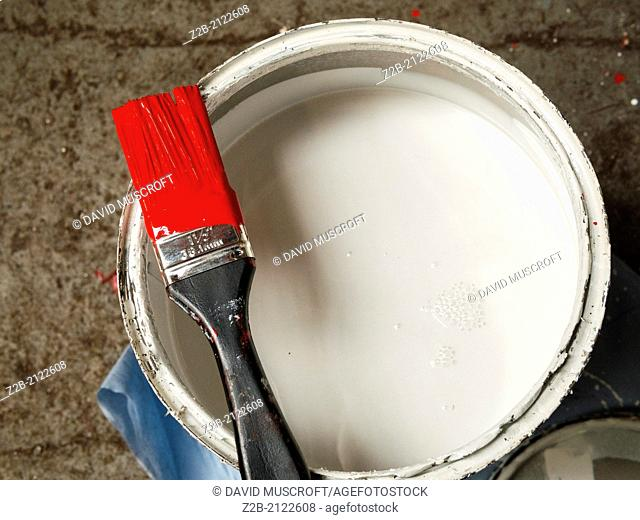 White paint tin with a paint brush holding red paint
