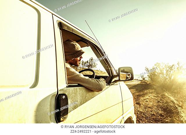 Candid and authentic travel portrait of a man seated in dirt covered camper van parked on a australian lookout watching sunset
