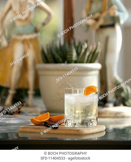 A glass of ginger beer with ice and an orange wedge
