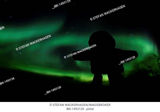 Silhouette of Inuit stone man, inukshuk, inuksuk, stone landmark or cairn, Northern Polar Lights, Aurora Borealis, green, near Whitehorse, Yukon Territory