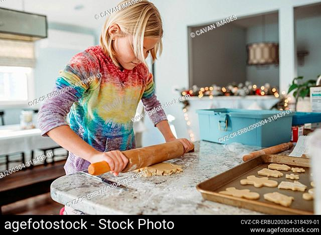 Girl rolling out cookie dough side view