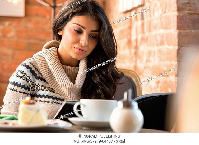 Young woman reading menu in a cafe indoors. Shallow depth of field