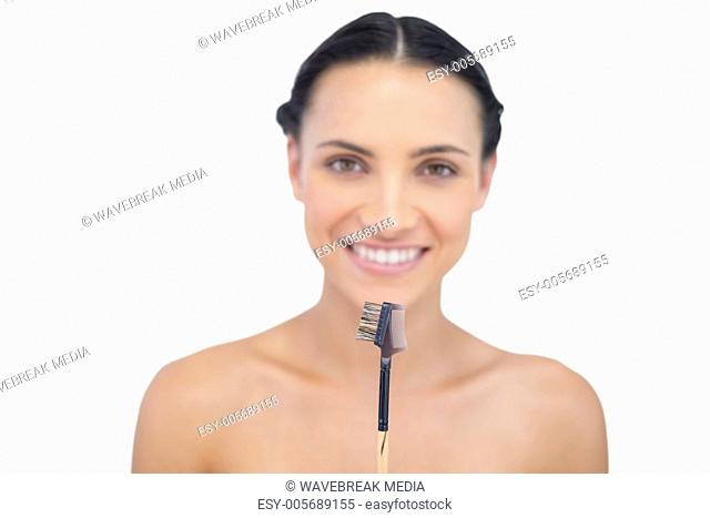 Smiling young model holding eyebrow brush