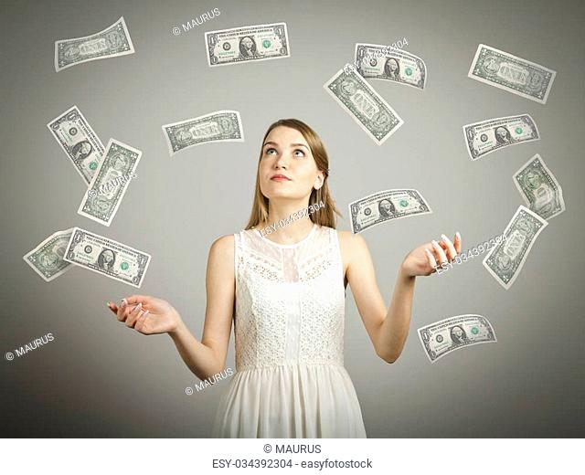 Girl in white and falling dollar banknotes. Currency and lottery concept