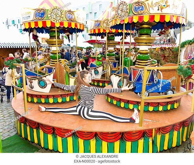 woman exercises urban yoga outdoor on a carousel at a fun fair