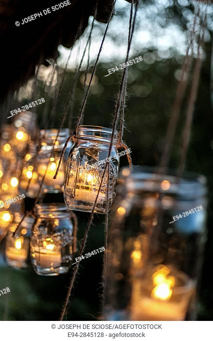 Hanging Mason jars holding lighted candles outdoors
