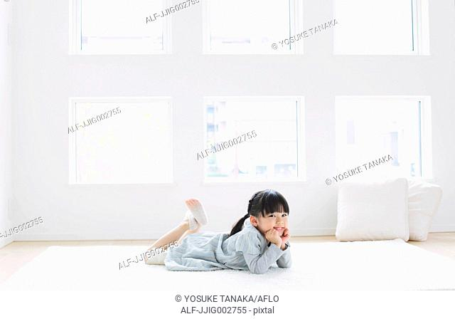 Elementary age girl laying on the floor by the window and smiling at camera
