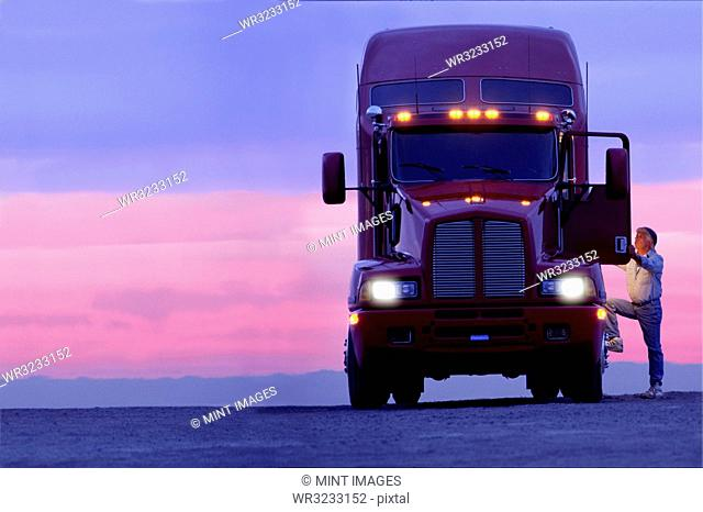 A silhouette of a truck driver getting into the cab of his commercial Class 8 truck tractor at sunrise