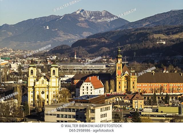 Austria, Tyrol, Innsbruck, elevated view of the Wilten Basilica and the Wilten Abbey Church, sunset, winter