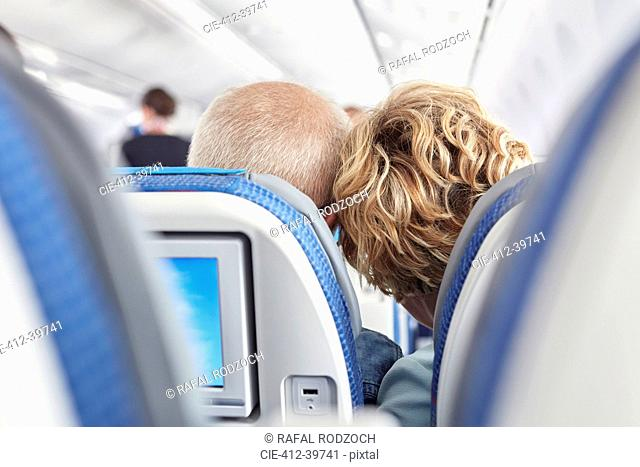 Rear view affectionate mature couple leaning on airplane
