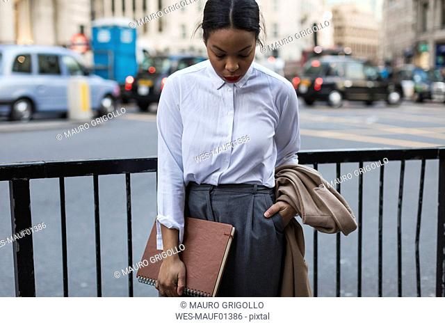 UK, London, businesswoman waiting on the street