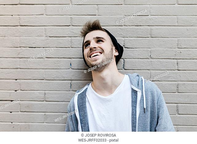 Young man laughing in front of wall, portrait