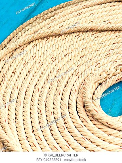 light braided rope part of marine fasteners, folded in a circle close-up, empty space in the middle