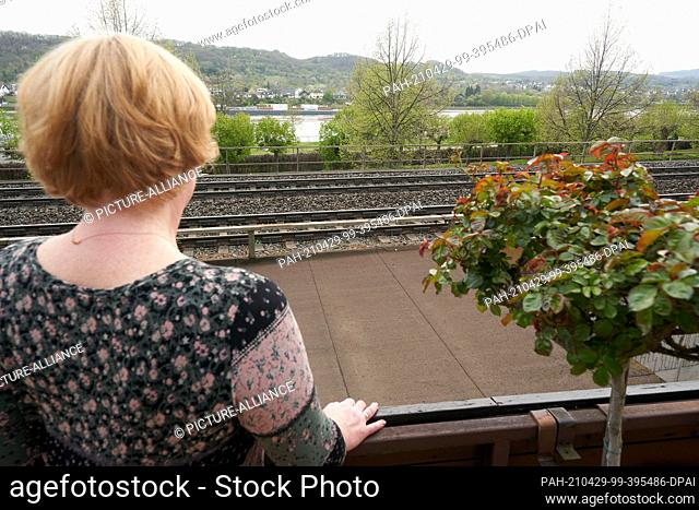 28 April 2021, Rhineland-Palatinate, Braubach: Monika Voß is standing on the balcony of the house near the railway tracks where she looks after her father