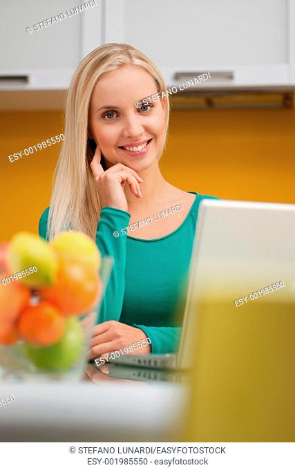 Beautiful young woman wotking on laptop in her kitchen