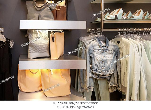Blouses, shirts and jackets hanging on rack in retail shop interior. Bags, handbags, shoulder bags on shelf