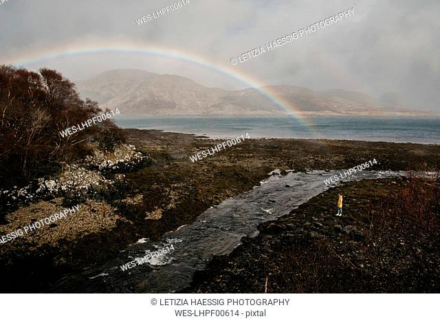 UK, Scotland, Highland, woman looking at rainbow above the sea