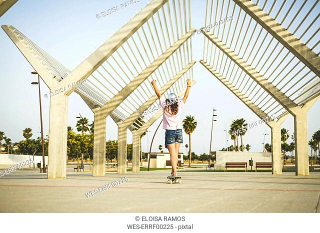 Girl on skateboard, raising arms, rear view