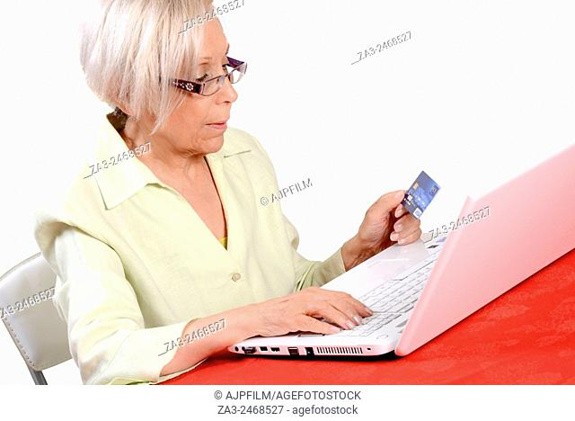 Elderly woman using her credit card to order a product online