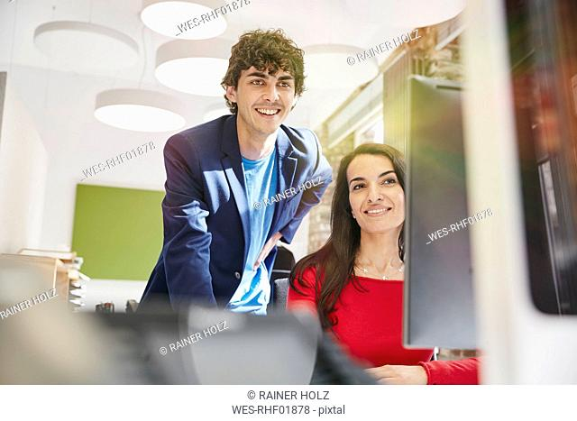 Young man and woman working together in office