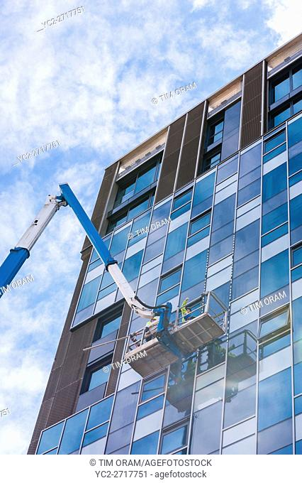 Men cleaning the windows of a high rise building in Norwich , Norfolk , England , Britain , Uk