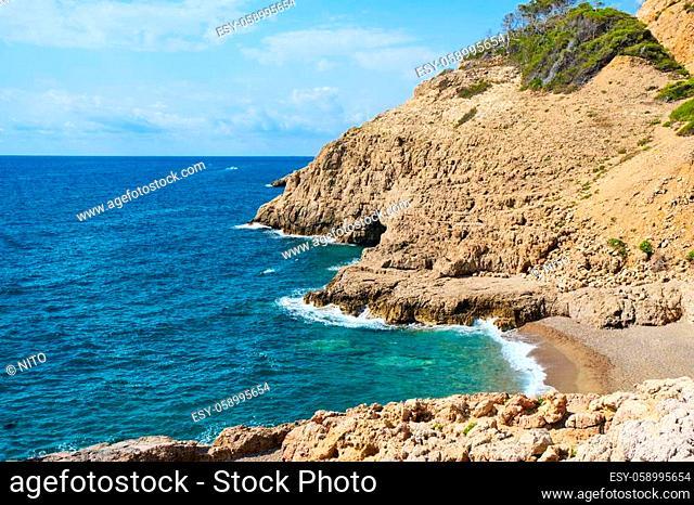 a view over the Llop Mari beach and the Llop Mari sea cave in Hospitalet del Infant, Spain, in the Costa Dorada coast