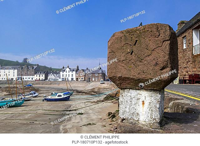 Old stone with sundial and sailing boats at low tide in the picturesque harbour of Stonehaven, Aberdeenshire, Scotland, UK