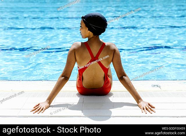 Back view of young woman wearing red swimsuit and swimming cap relaxing at poolside after swimming