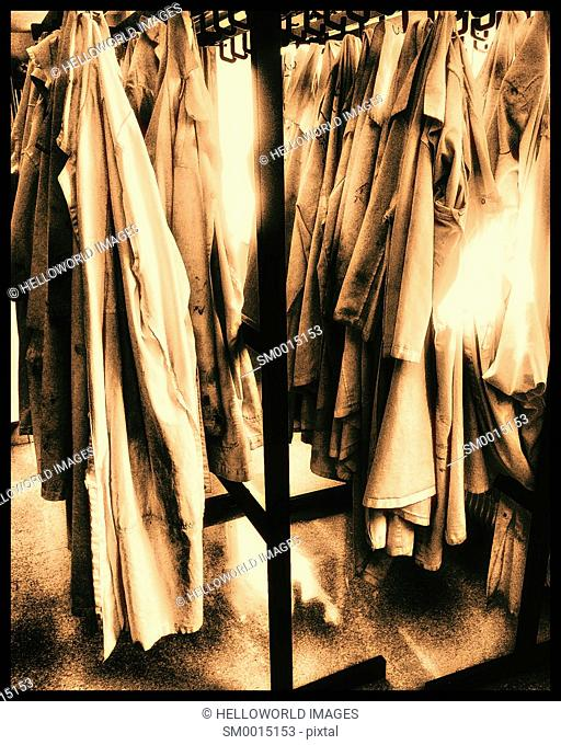 Rows of lab coats hanging up in sunlight