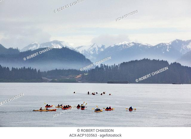 Large group of kayakers in the waters off Icy Strait Point, Hoonah, Alaska, U.S.A. The land mass in the background is the northeastern part of Chichagof Island...