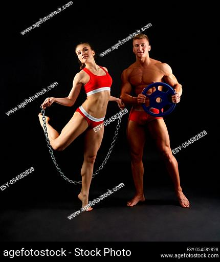 Young sexy sporty couple - a pretty woman and a fair man - dressed in red and white sports clothes studio shot black background