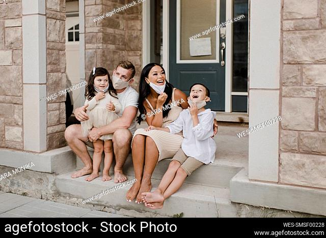 Smiling family with kids wearing protective face mask while sitting on steps outside house