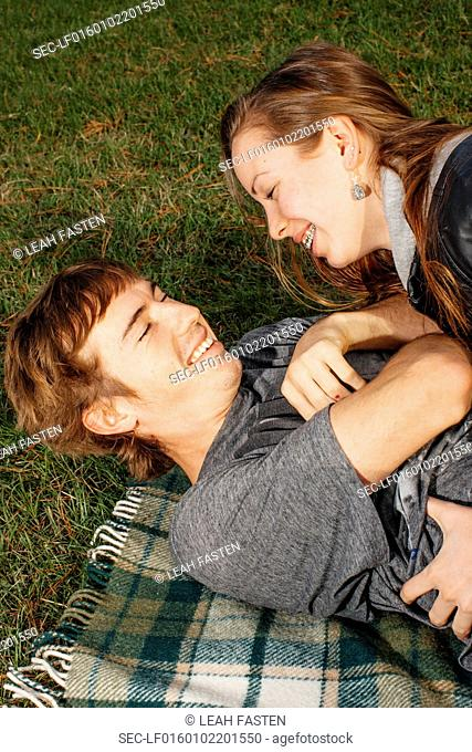 Boyfriend and girlfriend (16-17) lying down on blanket in park