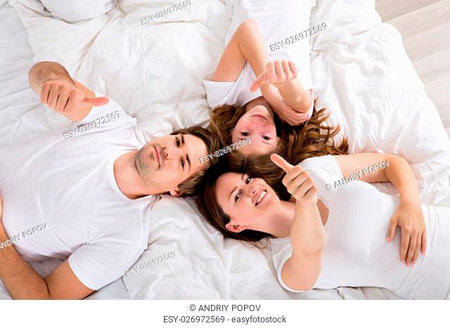 High Angle View Of A Happy Family Lying On Bed And Showing Thumbs Up
