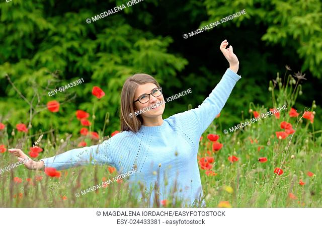 Young girl playing in a poppy field