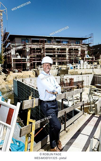 Portrait of smiling man wearing hard hat on construction site