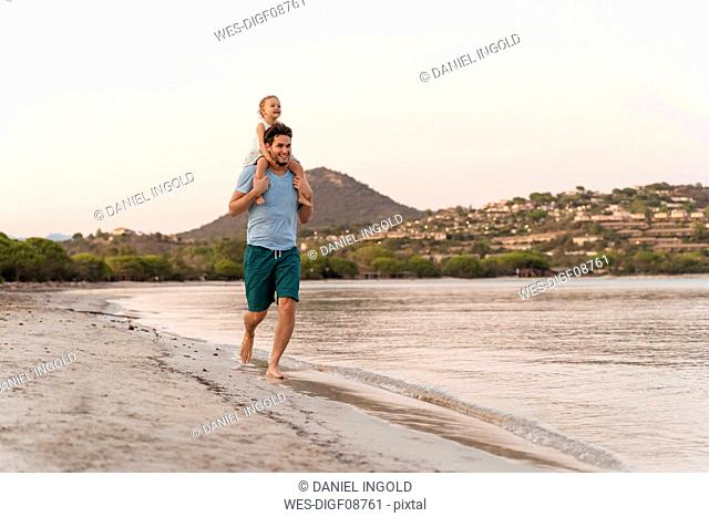 Happy father carrying daughter on shoulders on the beach at sunset