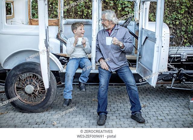 Senior man and boy having a coffee break at vintage car